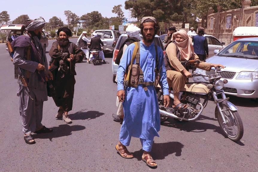 Молодой человек с Ближнего Востока в синем традиционном костюме идет посреди улицы с женщиной на мотоцикле позади.