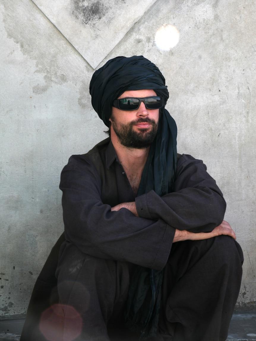 Сидит бородатый мужчина в черных очках, черном платке и черном костюме.
