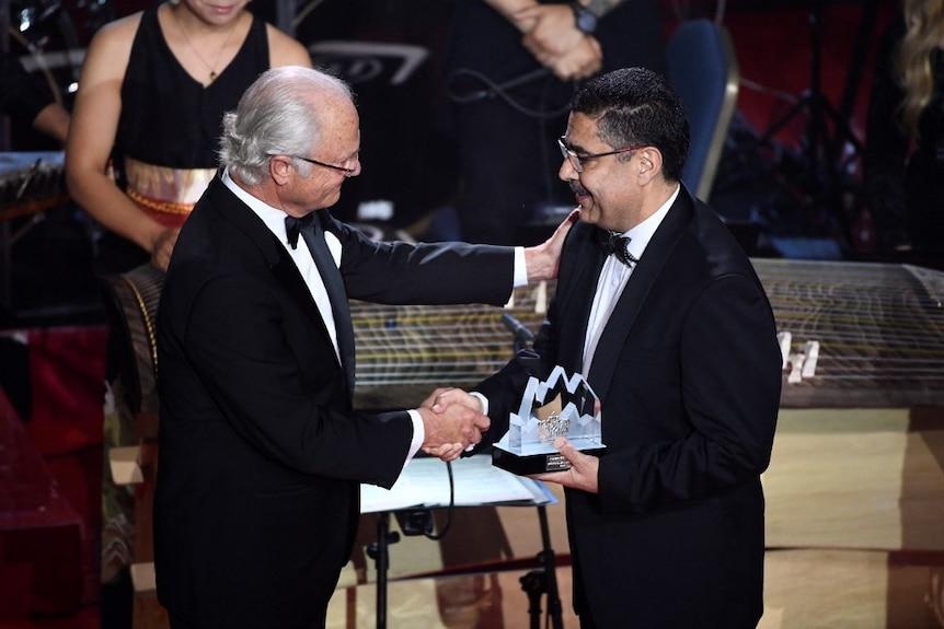 Двое мужчин в смокингах пожимают друг другу руки на сцене, один держит трофей