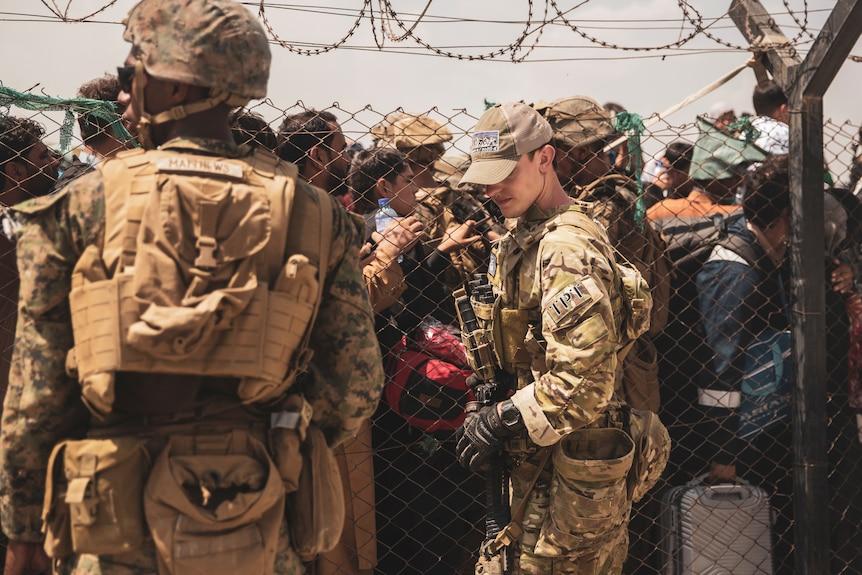 Американский солдат стоит на страже перед сетчатым забором, за которым стоят очереди десятки человек в аэропорту Кабула.